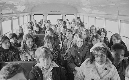 This is a photograph of two African American children and more than thirty white children riding in a school bus from the suburbs to an inner city school, Charlotte, North Carolina (1973).