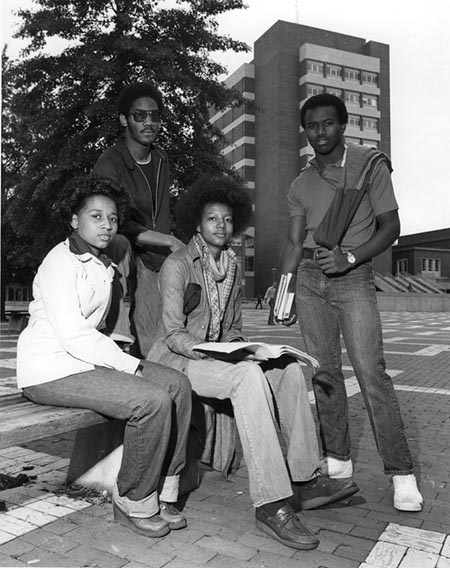 This is a photograph of four African American students sit outside of North Carolina State University's D.H. Hill Library in 1970.