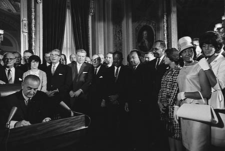 President Lyndon B. Johnson signs the Voting Rights Act as Martin Luther King Jr. and other civil rights leaders look on, August 6, 1965, United States Capitol, Washington, D.C.