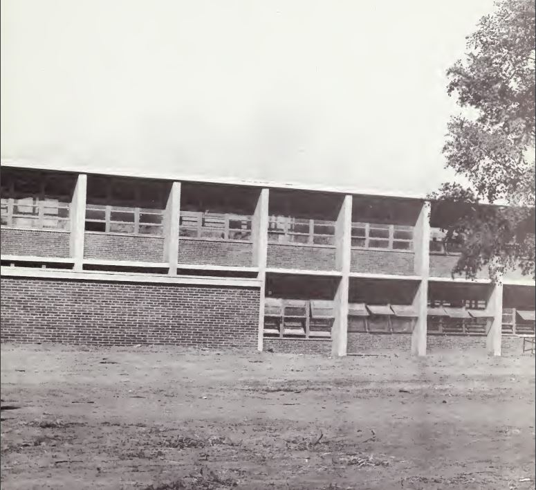 This is an image of the photo that appears on the first page of the 1966 West Charlotte High School yearbook. It shows a plain building with open windows and a lawn of dirt.