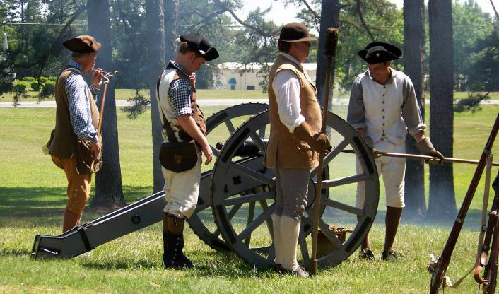 Image or reenactors at the Alamance Battleground, with a cannon