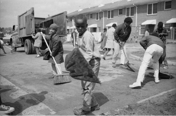 Photograph of men, women, and children using shovels and brooms to sweep a street during a clean-up campaign at McDougal Terrace in Durham, North Carolina, March, 1968.