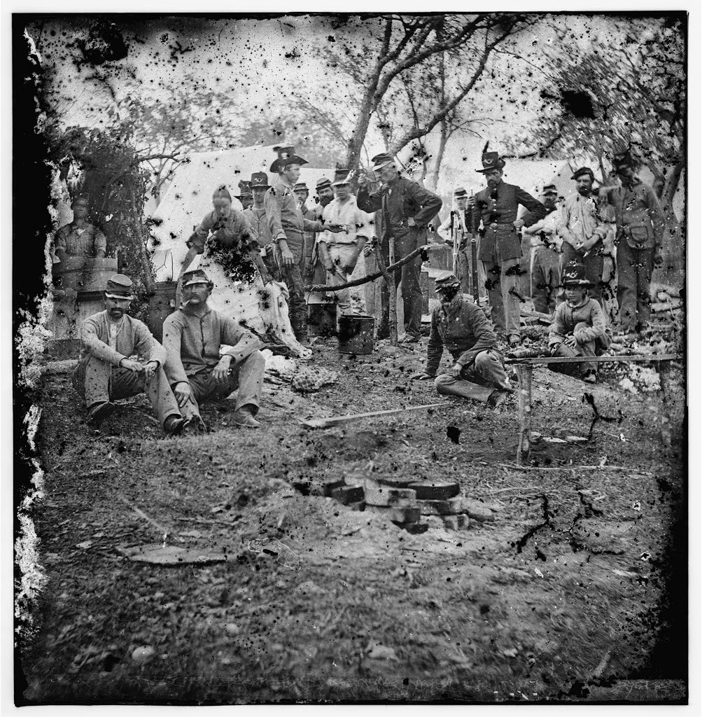 Civil War soldiers gathered around a fire, preparing food. At an encampment, a pot hangs from a frame made of sticks.