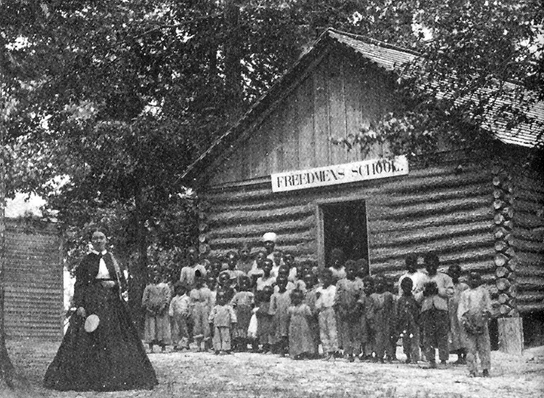 Photograph of a group of students standing outside James' Plantation School, a freedmen's school. Likely taken in October 1868.