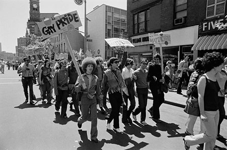Men and women carry Gay Pride signs as they march through the streets of a city.