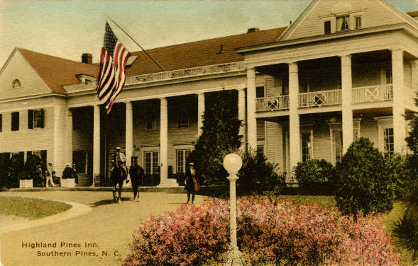 Postcard of the Highland Pines Inn in Southern Pines, N.C. showing a two-story inn with horses in front and an American flag waving in the wind.