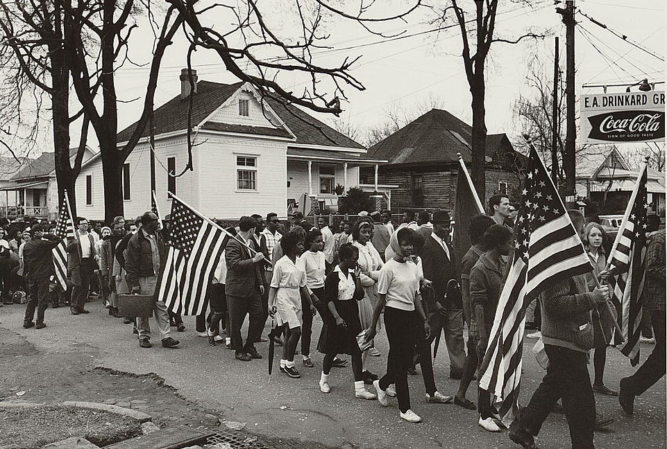 This is a photograph of demonstrators walking down a street during the civil rights march from Selma to Montgomery, Alabama in 1965.