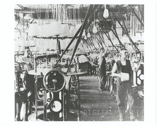Photograph inside of Hanes Knitting Factory; workers stand by machinery.