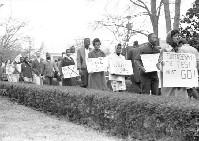 The is a photograph of Men and women in McComb, Mississippi march in a demonstration for voting rights in 1962.