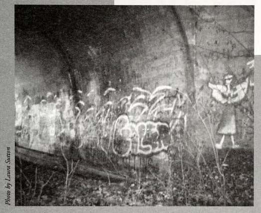 """Lydia is Here."" Photograph of drawing of angel and graffiti in the underpass to the abandoned bridge near E. Main Street in Jamestown, North Carolina. The ghost ""Lydia"" is believed to haunt the site.  Image from the North Carolina Folklore Journal, Midwinter 2000."