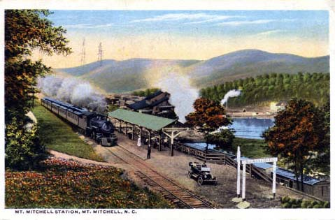 Postcard image of the Mt. Mitchell Station at Mt. Mitchell in North Carolina. Image ca. 1918.  Developed from the existing logging trains, the tourist railroad became one of the earliest and most popular tourist attractions in the state when it opened in 1915. During its four years of operation, more than 10,000 tourists were transported to Camp Alice which sits just below the summit of the mountain. There they could dine, camp and enjoy a short mile hike to the summit. The train and logging operations ceased by 1921 when the mountain slope forests had been depleted. Image from NC Postcards, UNC-Chapel Hill.