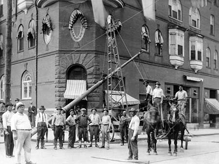 A Carolina Power and Light line crew seen posing for a photo at the corner of W. Martin and McDowell Streets in Raleigh on July 5, 1916 as they hoist up a light pole with a team of horses. From the CP&L Collection, State Archives of North Carolina. Used courtesy of the N.C. Department of Natural and Cultural Resources.