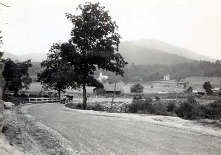 Photograph of a rural road and farm scene in North Carolina, ca. 1910-1910. Item H.19XX.317.4 from the N.C. Museum of History. Used courtesy of the N.C. Department of Natural and Cultural Resources.