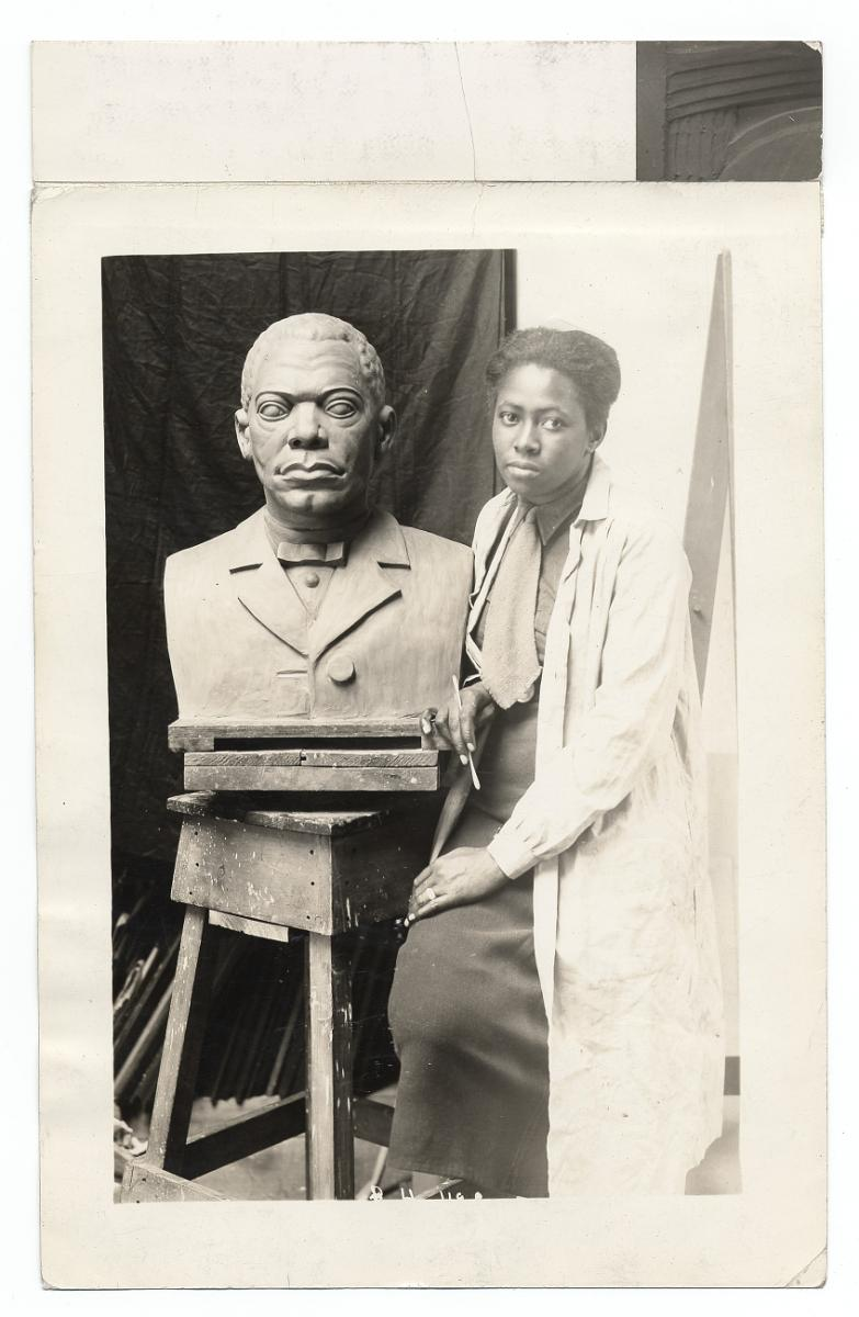 Portrait of Selma Burke seated next to her sculpture of Booker T. Washington. Taken during the 1930s while she was working for the WPA Federal Art Project. From the Archives of American Art, Smithsonian Institution.
