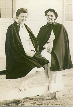 Snapshot of U.S. Army nurse Almyra M. Watson (left) and an unidentified nurse, wearing their Army Nurse Corps uniform and capes, sitting outside on a wooden fence on a beach next to a building at an unidentified military installation during World War II (from the John L. Watson Papers, WWII Papers, Military Collection, State Archives of North Carolina, Raleigh, N.C.).
