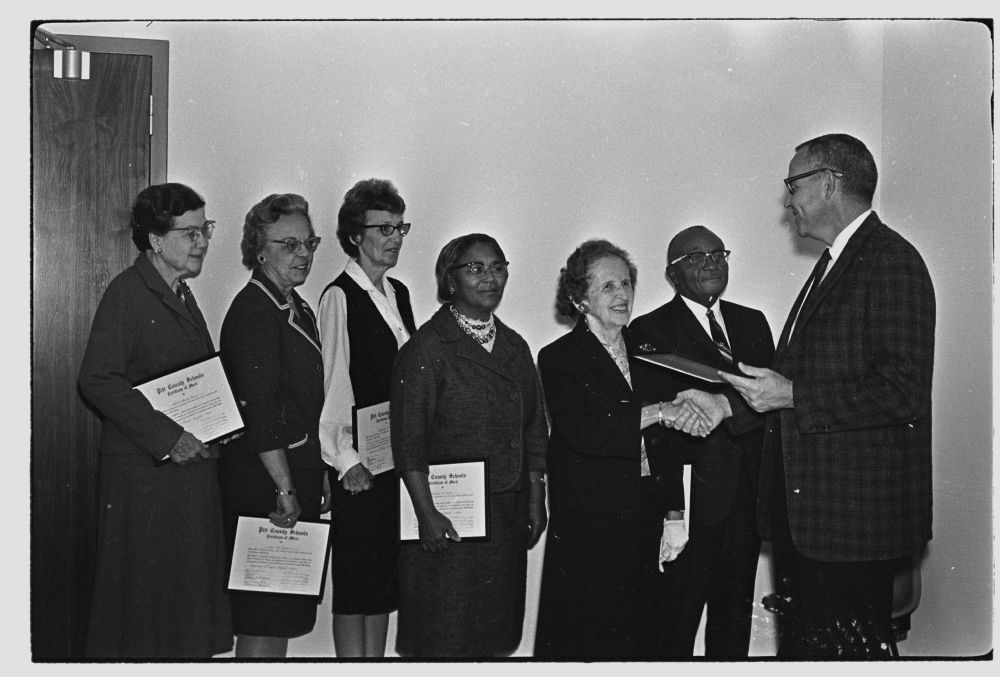 "Photograph of Pitt County Schools Superintendent Arthur S. ""Ott"" Alford (far right) presenting certificates to school system faculty and staff. This photograph is from the Daily Reflector Image Collection at ECU and is for use only in research, teaching, and private study."