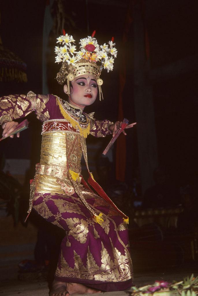 "<img typeof=""foaf:Image"" src=""http://statelibrarync.org/learnnc/sites/default/files/images/bali_232.jpg"" width=""686"" height=""1024"" alt=""Balinese girl dressed in purple and gold costume"" title=""Balinese girl dressed in purple and gold costume"" />"