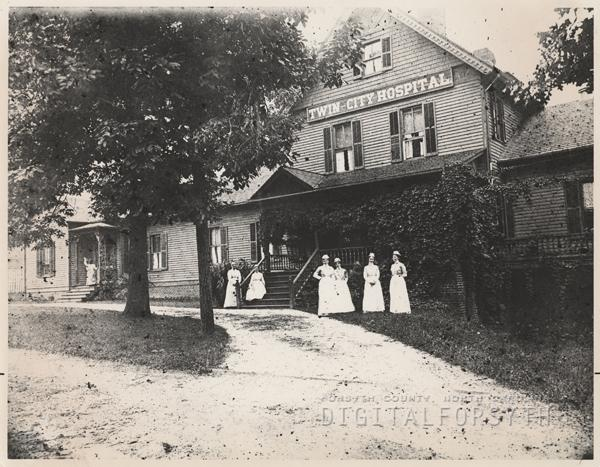 Nurses standing in front of the Twin City Hospital