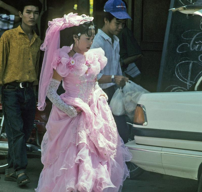 """<img typeof=""""foaf:Image"""" src=""""http://statelibrarync.org/learnnc/sites/default/files/images/vietnam_145.jpg"""" width=""""1024"""" height=""""975"""" alt=""""Bride walks through street in lacy pink wedding dress and high gloves at Mytho"""" title=""""Bride walks through street in lacy pink wedding dress and high gloves at Mytho"""" />"""
