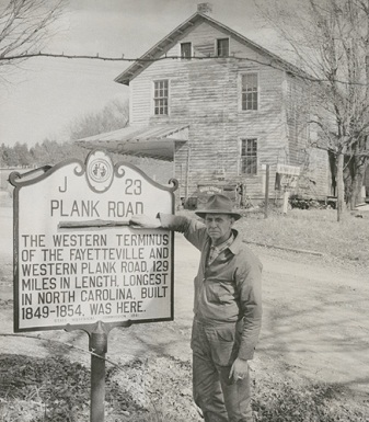 Mr. John A. Shore holding a piece of the plank road in front of the North Carolina Highway Historical Marker in Bethania, 1959. Mr. Shore owned the general store in the background.