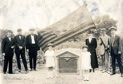 Photograph of a marker for Richard Caswell's grave, 1919. Fred A. Olds is holding the Guilford Courthouse Flag. Image from the North Carolina Museum of History.