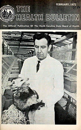 The cover of The Health Bulletin, February 1971. Dr. Jurgelsky removes an opossum from a nest box in the building developed at the National Institute of Environmental Health Sciences, Research Triangle Park,  to house the opossum breeding colony. Individual cages and nest boxes are seen to either side. In order to avoid a painful, and often severe bite on the hand, the animals must be restrained by quickly and firmly grasping the nape of the neck.