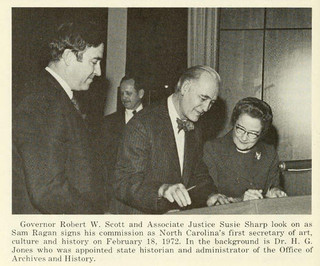 Governor Robert W. Scott, Associate Justice Susie Sharp, and Sam Ragan signing his commission as first Secretary of Art. Image from the Government & Heritage Library, State Library of N.C.