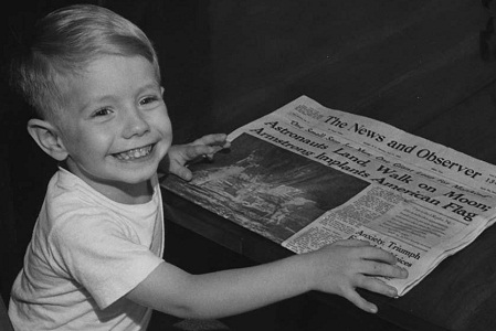 "PHOTO OF DWAYNE CLARK, AGE 3 1/2 YEARS OLD, SON OF MR. & MRS. CHARLES CLARK, HOLDING A COPY OF THE ""NEWS & OBSERVER,"" JULY 21, 1969, ANNOUNCING THE FIRST MOON LANDING"