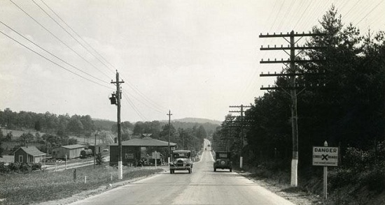 Road lined with electric and telephone poles, 1910-1920.