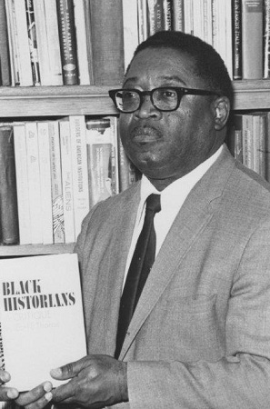 Photograph of Dr. Earlie Endris Thorpe holding a copy of his 1971 book, Black Historians- A Critique