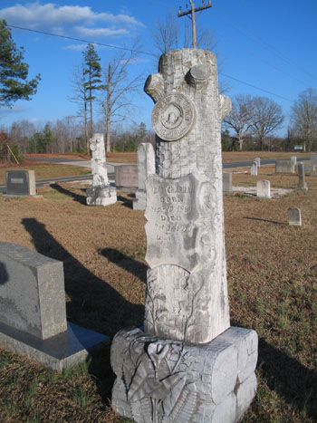 Log-shaped gravestone for a member of the Woodmen of the World, Wahaw, N.C. Image from Flickr user catchesthelight (BEV Norton).