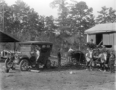 Cutting up corn for feed, using automobile for power about 1912.