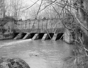 """View looking west at Sluice Gates at dam from north bank of Deep River- Lockville Hydroelectric Plant, Deep River, 3.5 miles upstream from Haw River, Moncure, Chatham County, NC."" Image courtesy of Library of Congress; call #: HAER NC,19-MONC,1--6."