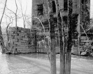 """View showing east elevation of powerhouse and masonry retaining walls- Lockville Hydroelectric Plant, Deep River, 3.5 miles upstream from Haw River, Moncure, Chatham County, NC."" Image courtesy of Library of Congress, call #: HAER NC,19-MONC,1--16."