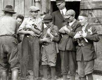 Students holding baby pigs, Farm School, 1908. Image courtesy of Warren Wilson Archives.