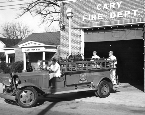 Three unidentified men with fire truck in front of the Cary, NC, Fire Department building, no date. From Carolina Power and Light (CP&L) Photograph Collection (Ph.C.68), North Carolina State Archives, call #:  PhC68_1_549_1.