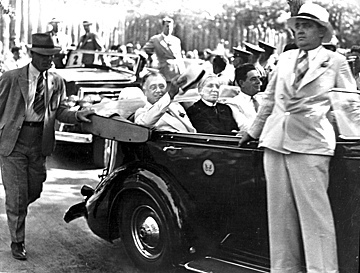 (L-R) President Franklin D. Roosevelt riding in open car with Governor Clyde Hoey and Congressman Lindsay C. Warren at the entrance to rebuilt Fort Raleigh, Manteo, NC, on or just before August 18, 1937, when he came to see the Lost Colony. From the State Archives of North Carolina, call #: ConDev57-314.
