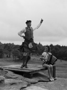 """Donald MacDonald dancing the Highland Fling while girl plays accordion at first Highland Games in 1956 near Grandfather Mountain, NC."" Photographed by Hugh Morton. Image courtesy of UNC- Chapel Hill Libraries."