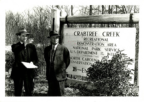 Fred Johnson (left) and Bruce Etheridge in 1943 at the transfer of Crabtree Creek Recreational Demonstration Area from the National Park Service to the North Carolina Division of State Parks. From the North Carolina State Parks Collection, NC Digital Collections.