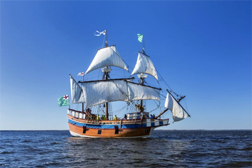 Photograph of the <i>Elizabeth II</i>, a representational ship launched in 1983 for the 400th anniversary of the Roanoke Voyages in 1984.  The ship is moored at Festival Park in Manteo, NC and is a composite representing the characteristics of the merchant ships of the Roanoke Voyages. Image by Jay Watkins, NC ECHO, courtesy of the North Carolina Department of Cultural Resources.