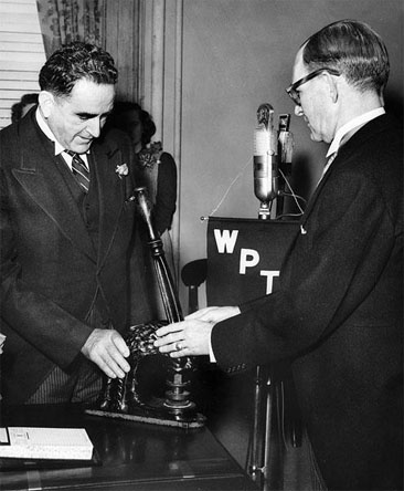 Photograph of Gov. Bott Scott passing the Great Seal of NC to Gov. William Umstead, January 1953.  Item H.1966.109.14 from the North Carolina Museum of History. Used courtesy of the Department of Cultural Resources.