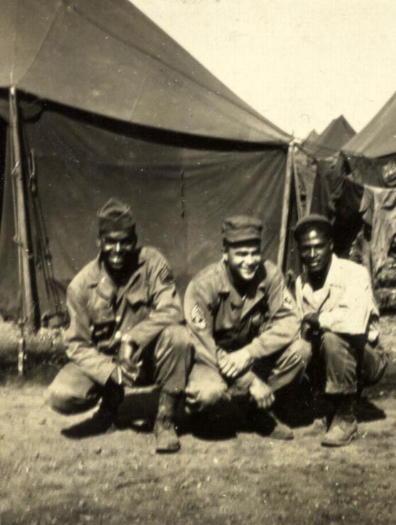"This is a black and white print of soldiers crouching with tents in the background, Fort Francis E. Warren, Wyoming, 1943. Soldiers from left to right are ""unidentified,"" First Sergeant Southall, and Odra W. Bradley."