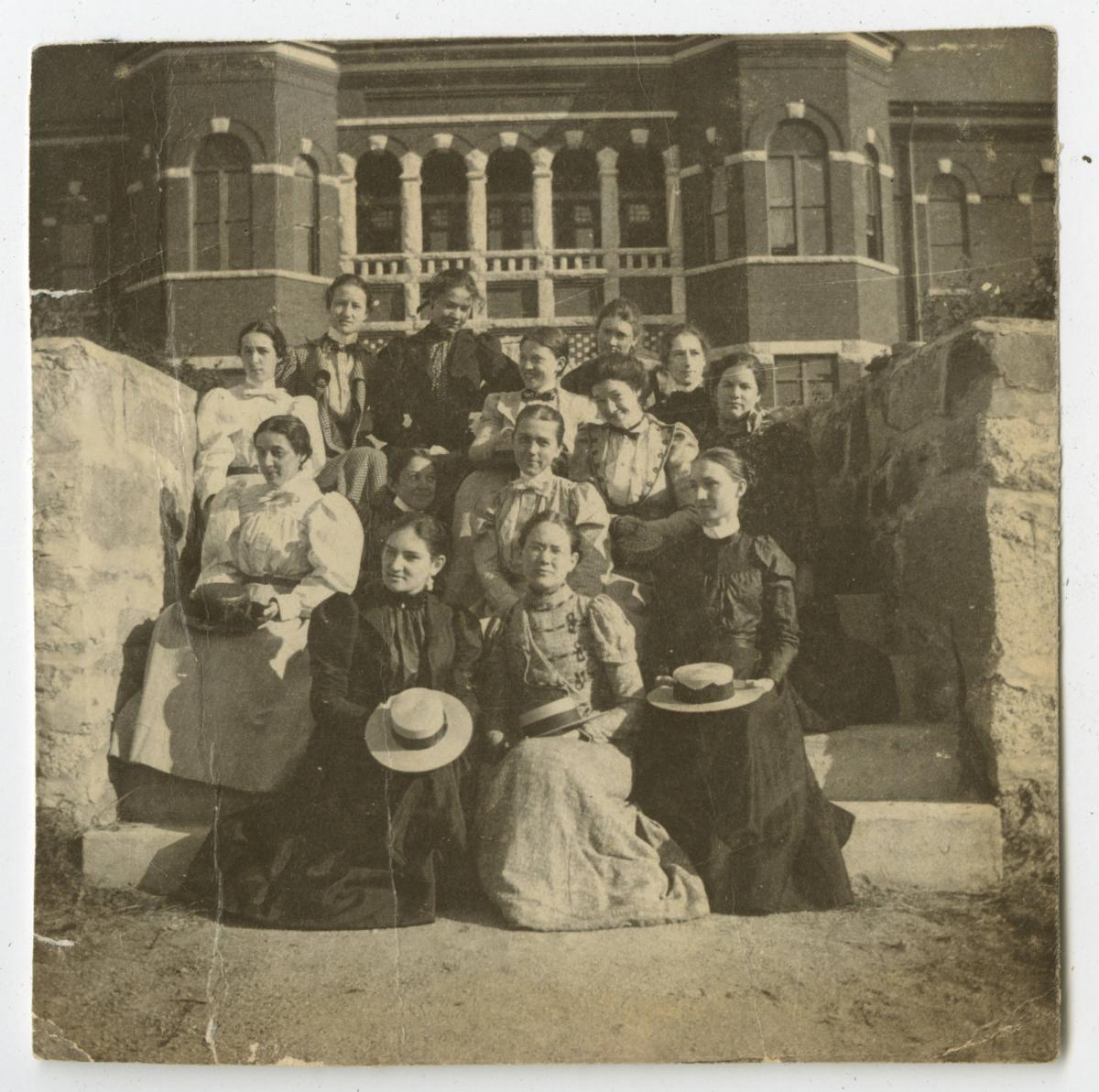 Thirteen students sit on the steps of a campus building for a group photo.