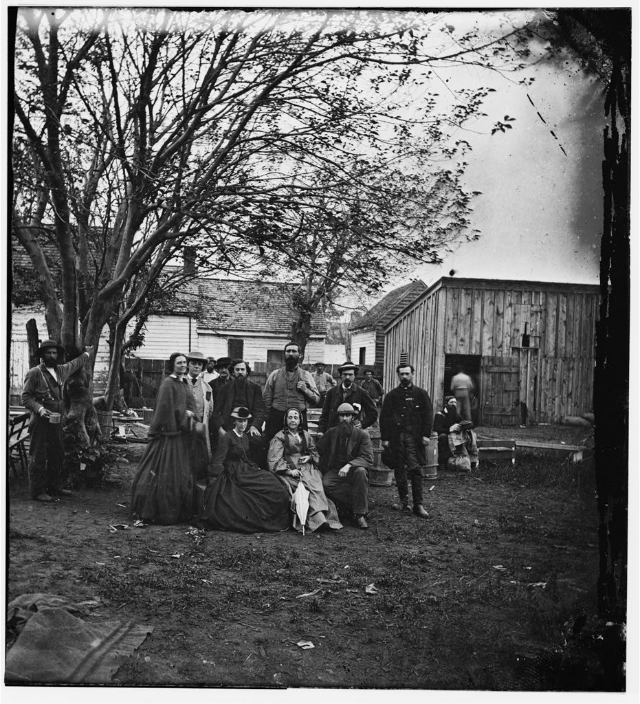 Nurses and officers of the U.S. Sanitary Commission pose under a tree in Fredericksburg, Virginia.