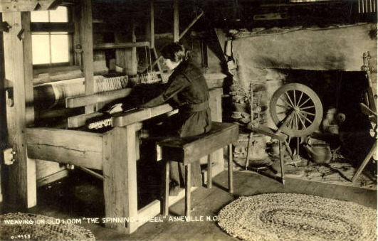 A woman weaves on a wooden loom.
