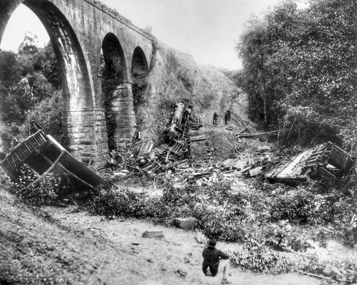 The locomotive and remains of wooden passenger cars at the base of the 60-foot-high Bostian Bridge over Third Creek near Statesville. Photograph by William Stimson, courtesy of Betty Boyd. North Carolina Collection, University of North Carolina at Chapel Hill Library.