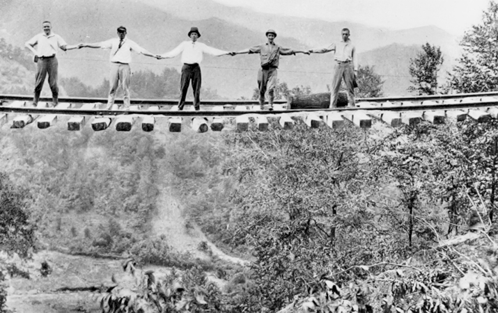 Men standing on a railroad bridge in McDowell County after its center supports had been washed away during the great western North Carolina floods of July 1916. North Carolina Collection, University of North Carolina at Chapel Hill Library.