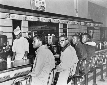 Students from North Carolina Agricultural and Technical College sit in at the whites-only lunch counter at the F. W. Woolworth store in downtown Greensboro on 1 Feb. 1960. Left to right: Ezell Blair, Franklin McCain, David Richmond, and Joseph McNeil. Greensboro News and Record.