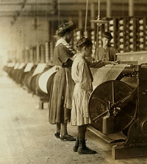 """Girls running warping machines in Loray mill, Gastonia, N.C. Many boys and girls much younger. Boss carefully avoided them, and when I tried to get a photo which would include a mite of a boy working at a machine, he was quickly swept out of range. 'He isn't working here, just came in to help a little.' Location: Gastonia, North Carolina. Taken in November 1908 by National Child Labor Committee (U.S.)"