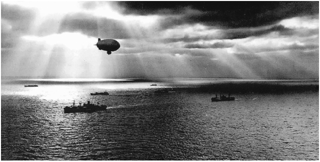 A U.S. Navy blimp flies over a convoy of ships to protect it from German U-boats. Image courtesy of Stephen D. Chalker.
